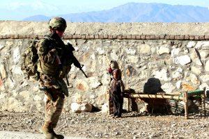 Children Look at a Female U.S. Soldier on Patrol