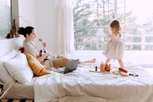 happy young woman playing with daughter at home