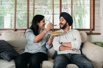 Happy Woman Feeding Ethnic Man